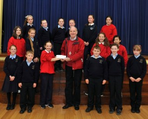 Pupil present cheque to John McCauley, proceeds from the Hallowe'en Disco, for the Amani Orphange in Tanzania